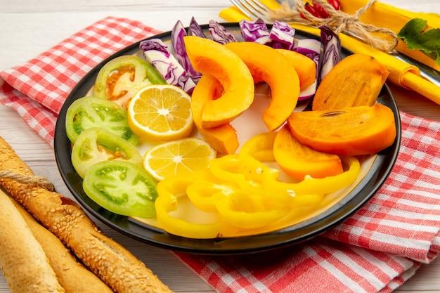 Onderaanzicht gehakte groenten en fruit kaki pompoen citroenen groene tomaten paprika op zwarte plaat rode peper poeder zeezout zwarte peper in kleine kommen brood op tafel