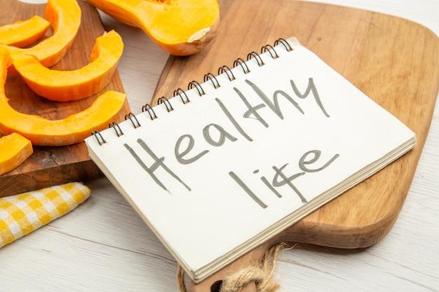 Onderaanzicht gehakte pompoen op snijplank gezond leven geschreven op notitieblok op snijplank op grijze tafel