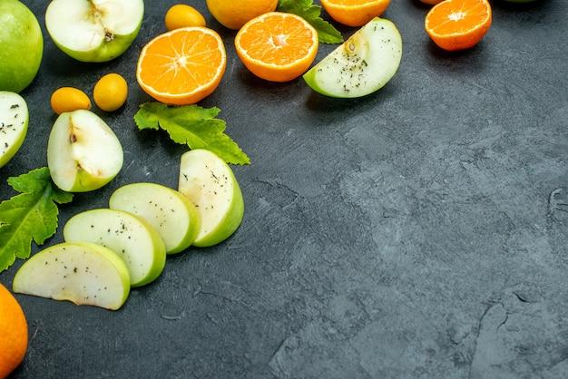 Onderaanzicht gehakte vruchten sinaasappels cumcuat appels met muntpoeder op donkere grond vrije ruimte