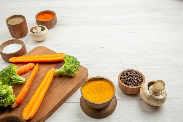 Onderaanzicht gehakte wortelen en broccoli op snijplank champignons verschillende kruiden in kommen op tafel vrije plaats