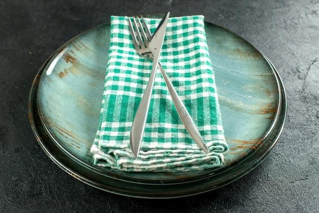 Onderaanzicht gekruist diner mes en vork op groen en wit geruit servet op schalen op zwarte tafel