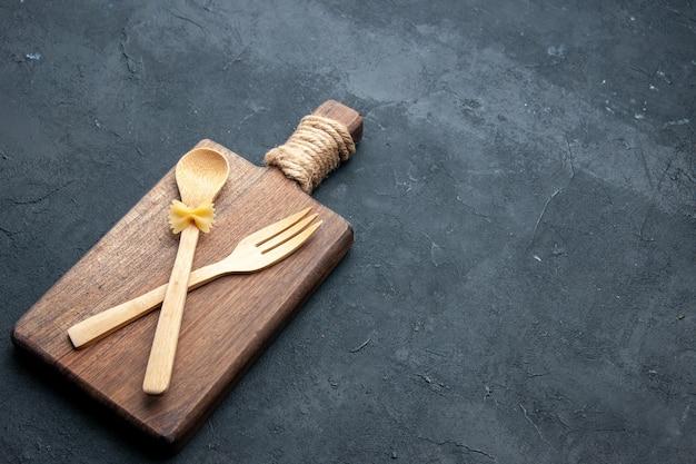 Onderaanzicht gekruiste houten lepel en vork op houten serveerplank op donkere ondergrond met vrije ruimte