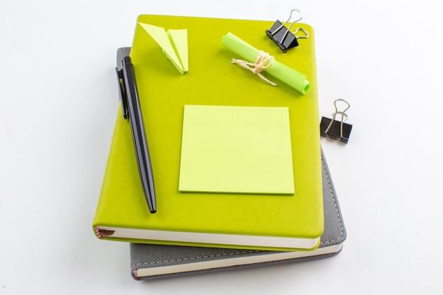 Onderaanzicht gele plaknotitie bindmiddel clips zwarte pen op blocnotes op witte tafel