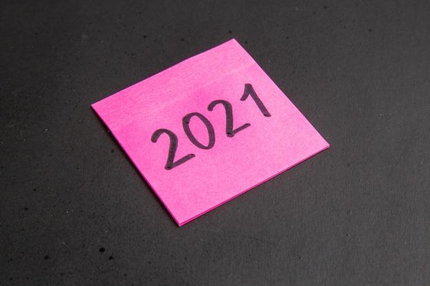 Onderaanzicht geschreven op roze kleverige nota op zwarte achtergrond