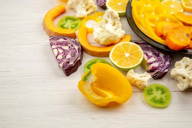 Onderaanzicht gesneden groenten en fruit pompoen paprika persimmon rode kool groene tomaten op plaat op houten tafel