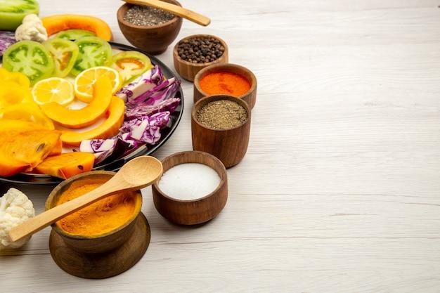 Onderaanzicht gesneden groenten en fruit pompoen paprika persimmon rode kool op zwarte plaat kruiden in kleine kommen houten lepel op houten tafel kopie ruimte