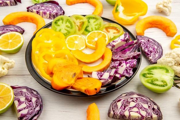 Onderaanzicht gesneden groenten en fruit pompoen persimmon gele paprika rode kool citroen groene tomaten op zwarte ronde schotel op witte tafel
