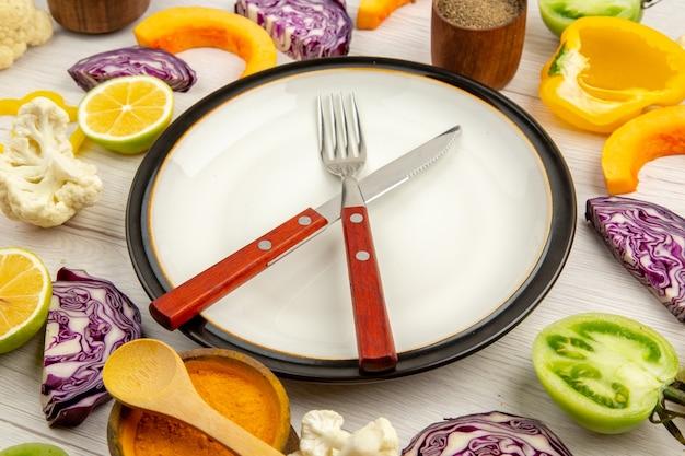 Onderaanzicht gesneden groenten pompoen rode kool citroen groene tomaten bloemkool gele paprika gekruiste mes en vork op plaat kruiden in kleine kommen op tafel