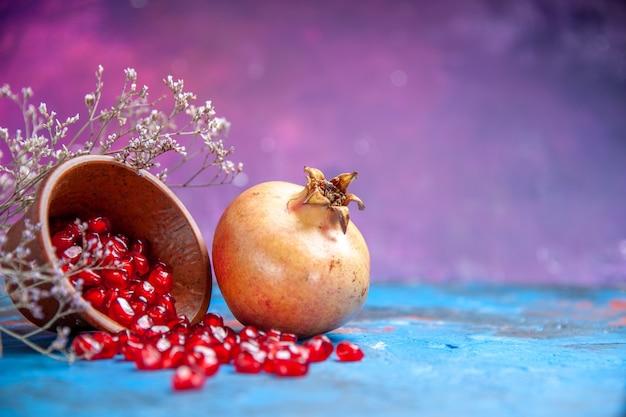 Onderaanzicht granaatappelpitjes in houten kom een granaatappel op paarse vrije plaats