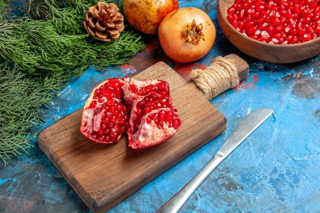 Onderaanzicht granaatappelzaden in kom diner mes een gesneden granaatappel op snijplank boomtakken op blauwe achtergrond