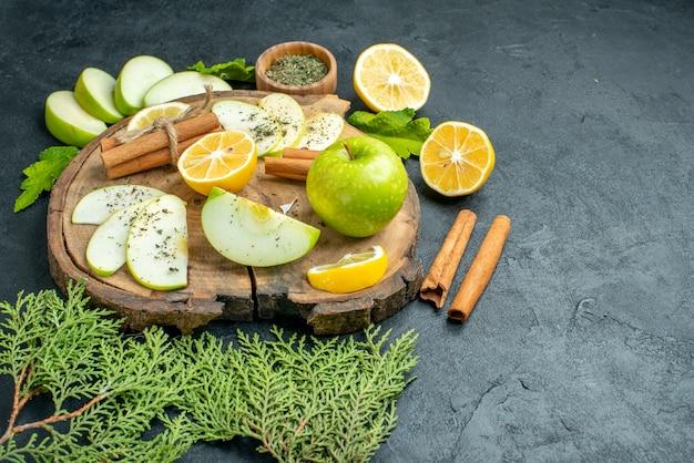 Onderaanzicht groene appel kaneelstokjes appel en citroen schijfjes op houten plank dennenboomtak in kom op zwarte tafel