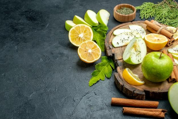 Onderaanzicht groene appels kaneelstokjes citroen en appelschijfjes op houten bord gedroogd muntpoeder in houten kom op zwarte tafel kopieerruimte