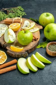 Onderaanzicht groene appels kaneelstokjes en schijfjes citroen appelschijfjes op een houten bord gesneden citroenen appels op zwarte tafel