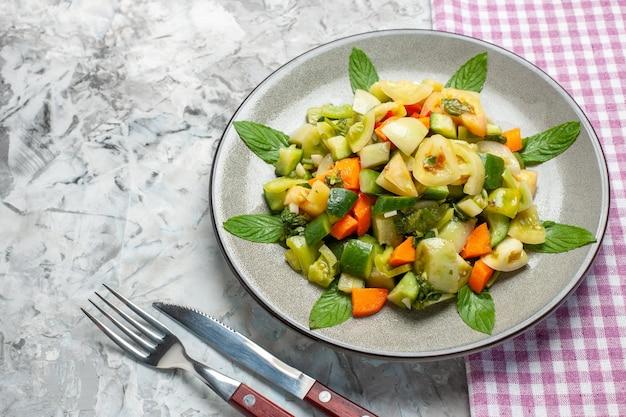 Onderaanzicht groene tomatensalade op ovale plaat een vork een mes op donkere achtergrond