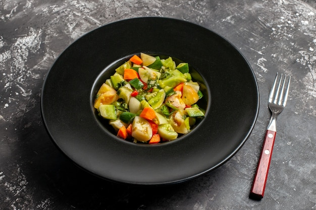 Onderaanzicht groene tomatensalade op ovale plaat een vork op donkere achtergrond