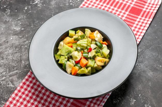 Onderaanzicht groene tomatensalade op ovale plaat op donker