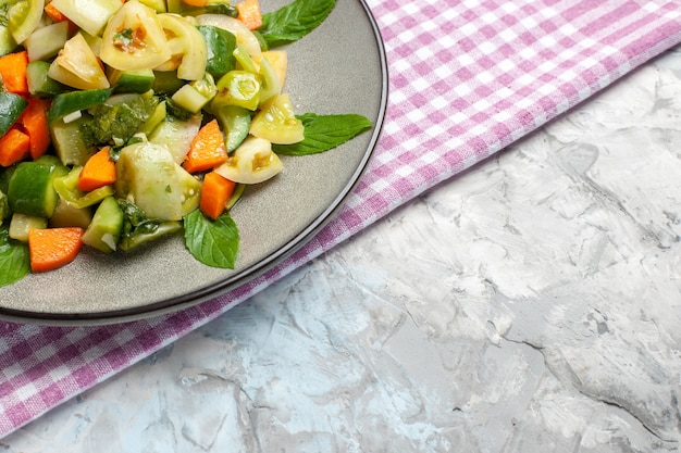 Onderaanzicht groene tomatensalade op ovale plaat roze tafelkleed op grijze achtergrond