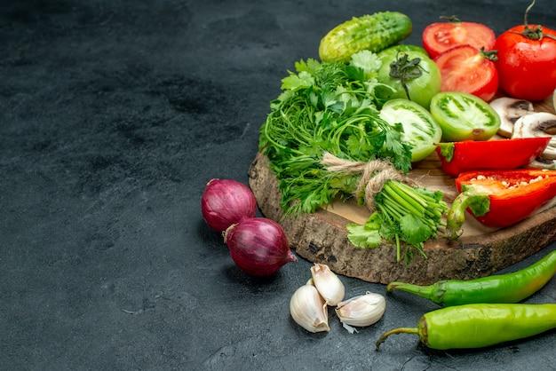 Onderaanzicht groenten champignons rode en groene tomaten paprika greens op rustieke bord rode uien hete pepers knoflook op zwarte tafel vrije ruimte