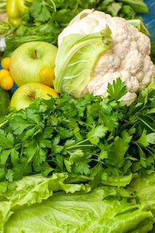 Onderaanzicht groenten en fruit peterselie sla cumcuat koriander bloemkool appels op de grond