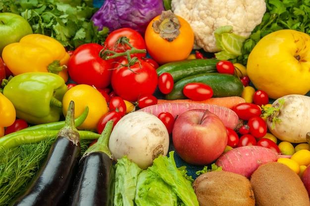 Onderaanzicht groenten en fruit radijs kerstomaatjes persimmon tomaten kiwi komkommer appels rode kool peterselie kweepeer aubergines op blauwe tafel