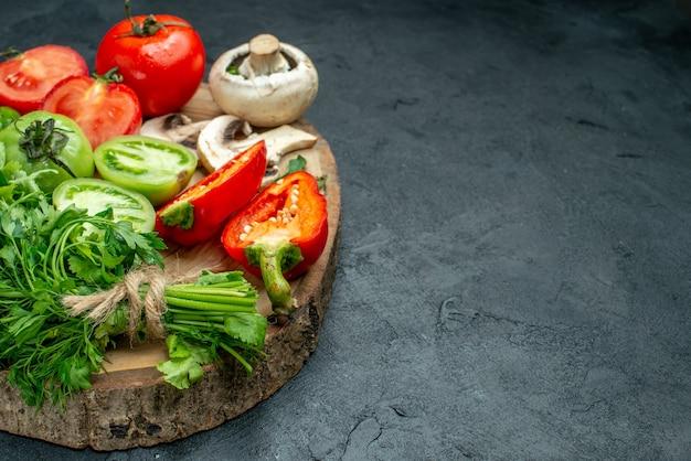Onderaanzicht groenten tomaten paprika greens paddestoel op houten bord op zwarte tafel vrije ruimte