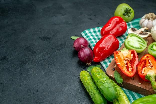 Onderaanzicht groenten tomaten paprika op snijplank knoflook komkommers rode ui op zwarte tafel met kopieerplaats