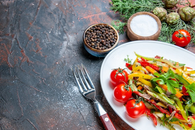 Onderaanzicht groentesalade op ovale plaat cherrytomaatjes vork zwarte peper en zout op donkerrode tafel vrije ruimte