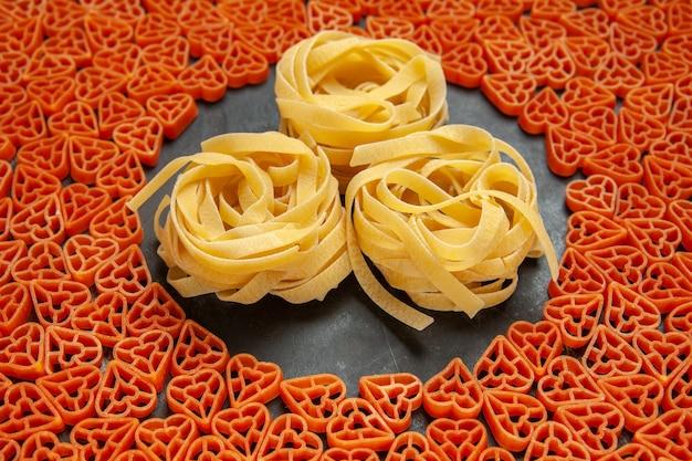Onderaanzicht hartvormige italiaanse pasta tagliatelles op lege plaats op donkere ondergrond
