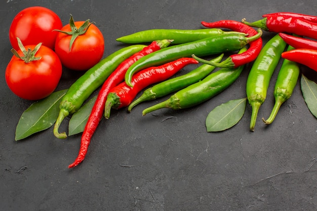 Onderaanzicht hete rode en groene paprika rode tomaten laurierblaadjes op zwarte achtergrond