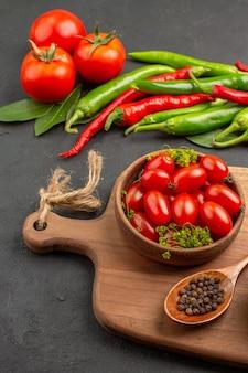 Onderaanzicht hete rode en groene paprika's en tomaten laurierblaadjes een kom met cherrytomaatjes en zwarte peper in een lepel op een snijplank op zwarte grond