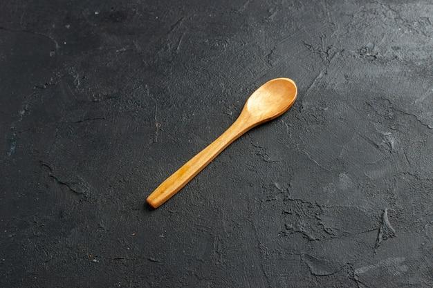 Onderaanzicht houten lepel op donkere tafel vrije ruimte