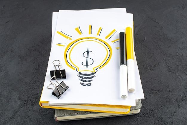 Onderaanzicht ideeën gloeilamp op notitieblok gele en zwarte markeringen bindmiddel clips op zwarte achtergrond