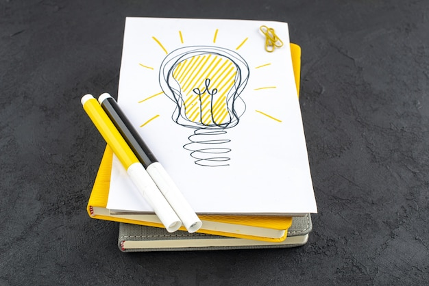 Onderaanzicht ideeën gloeilamp op notitieblok gele en zwarte markeringen edelsteen clips op zwarte achtergrond