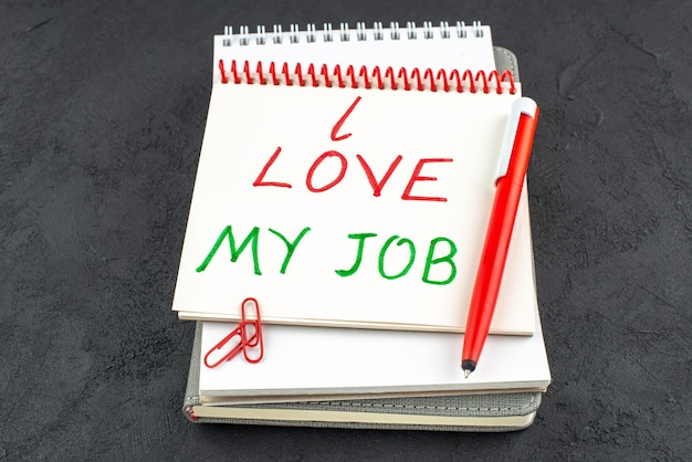 Onderaanzicht ik hou van mijn werk geschreven op spiraalvormige notebook rode pen edelsteen clips op donkere achtergrond