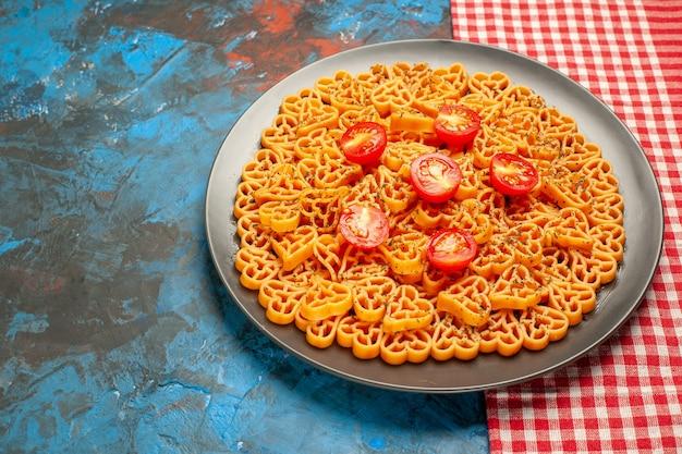 Onderaanzicht italiaanse pastaharten gesneden kerstomaatjes op bord op rood-wit geruite tafel