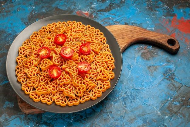 Onderaanzicht italiaanse pastaharten gesneden kerstomaatjes op plaat op snijplank op blauwe tafel