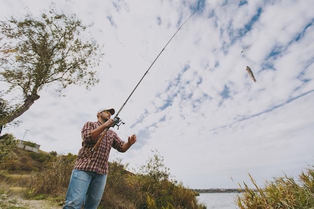 Onderaanzicht jonge ongeschoren man in geruit hemd, pet en zonnebril trekt een hengel met gevangen vis op een meer vanaf de kust in de buurt van struiken en riet. lifestyle, recreatie, vrije tijd concept.