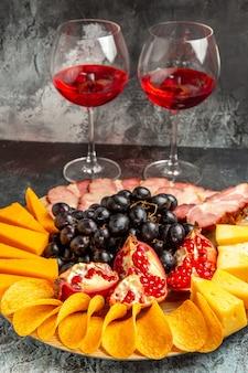 Onderaanzicht kaas stukjes vlees druiven en granaatappel op ovale serveerplank wijnglazen op donkere achtergrond
