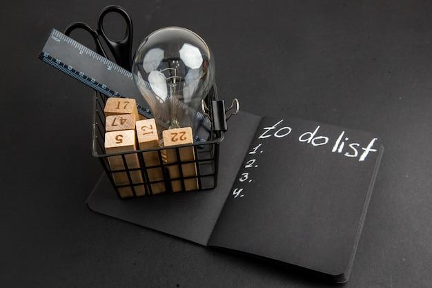 Onderaanzicht kantoorbenodigdheden in pennenetui takenlijst geschreven op zwart notitieblok op zwarte tafel