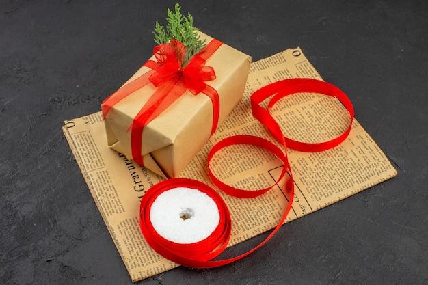 Onderaanzicht kerstcadeau in bruine papieren tak dennenlint op krant op donker
