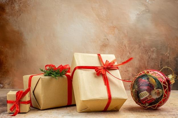 Onderaanzicht kerstcadeaus in bruin papieren lint kerstboom speelgoed op krant op donkere achtergrond
