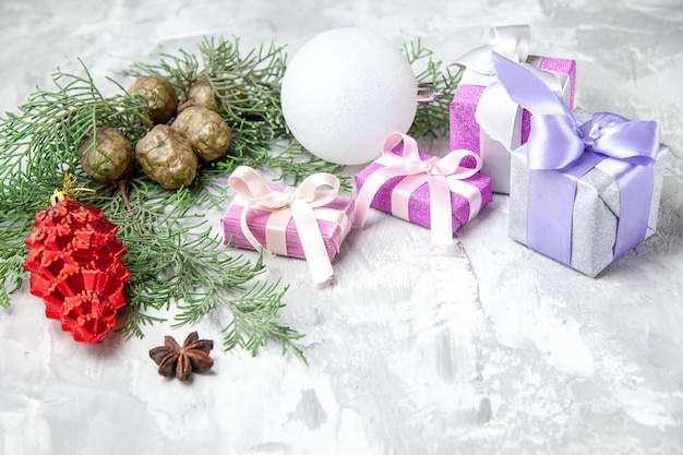 Onderaanzicht kerstcadeaus kerstboom speelgoed pijnboomtakken op grijs