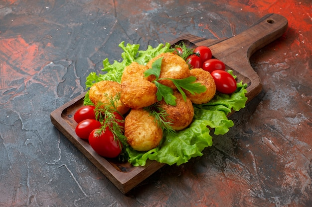 Onderaanzicht kipnuggets sla cherrytomaatjes op snijplank op donkere tafel met kopieerruimte