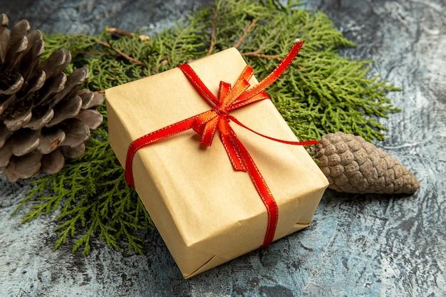 Onderaanzicht klein cadeautje gebonden met rood lint op dennentakken kegels op donkere achtergrond