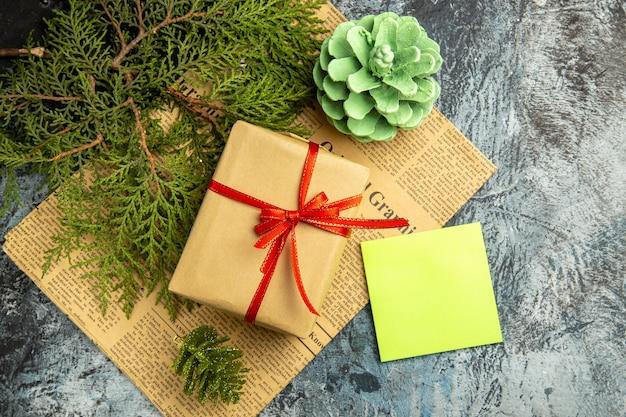 Onderaanzicht klein cadeautje gebonden met rood lint op krant gekleurde dennenappel op donkere achtergrond