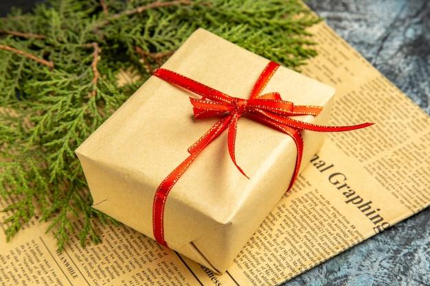Onderaanzicht klein cadeautje vastgebonden met rood lint dennentak op krant op donker