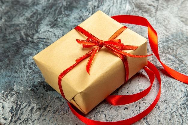 Onderaanzicht klein cadeautje vastgebonden met rood lint op donker