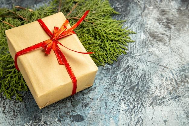 Onderaanzicht klein cadeautje vastgebonden met rood lint op pijnboomtakken op donker
