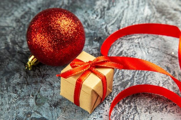 Onderaanzicht klein cadeautje vastgebonden met rood lint rode kerstbal op donker