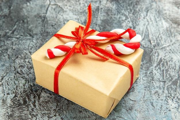 Onderaanzicht klein cadeautje vastgebonden met rood lint xmas snoep op grijze achtergrond